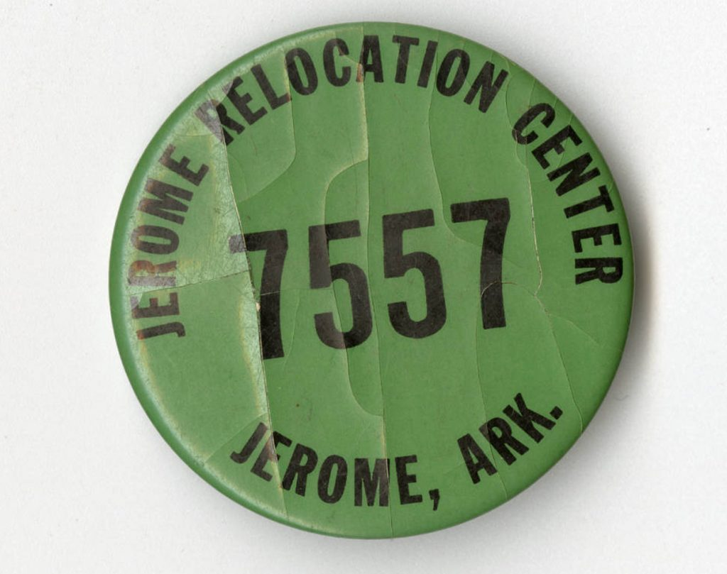 Photograph of a Jerome incarceration camp button that belonged to the Nakano family. The button is numbered 7557. Back of button reads: George Nakano 10-27-1942-09-25-1943.